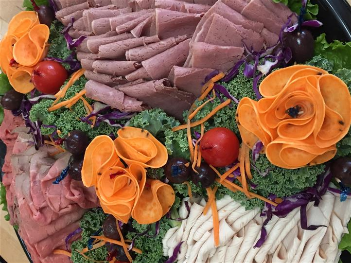 catering platter with cold cuts, and decorated veggies