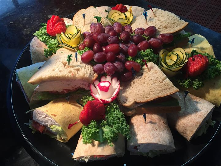 catering platter with cold cuts sandwiches, and decorated veggies
