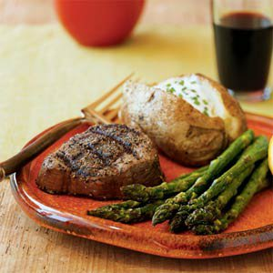 steak with a baked potato and asparagus
