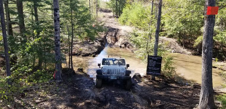 a jeep truck driving through mud in a forest