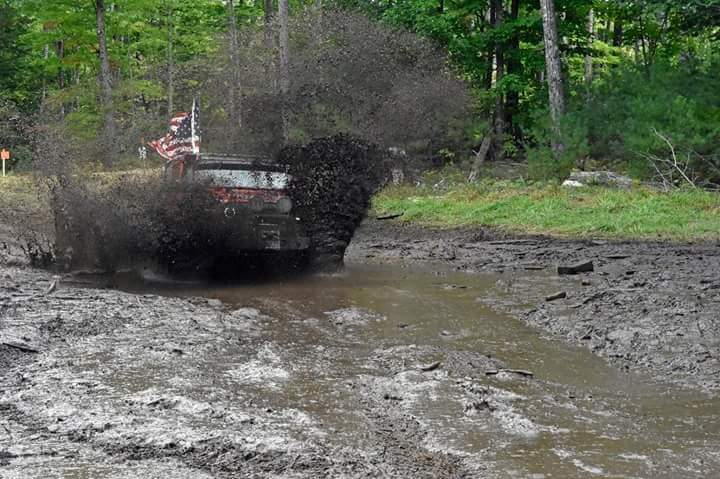 a jeep truck driving through and splashing mud