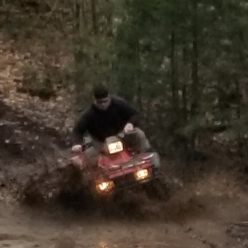 man driving an atv through the forest