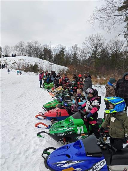 children lined up in snowmobiles