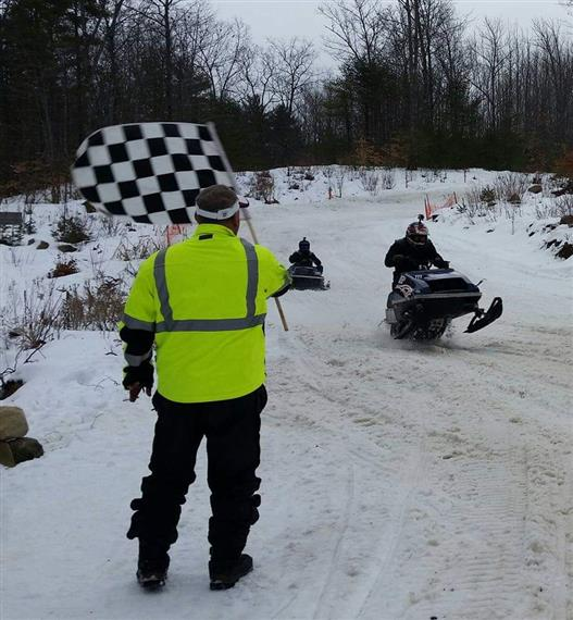 man waving racing flag as snowmobiles race