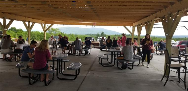 people eating in an outdoor patio area with roof