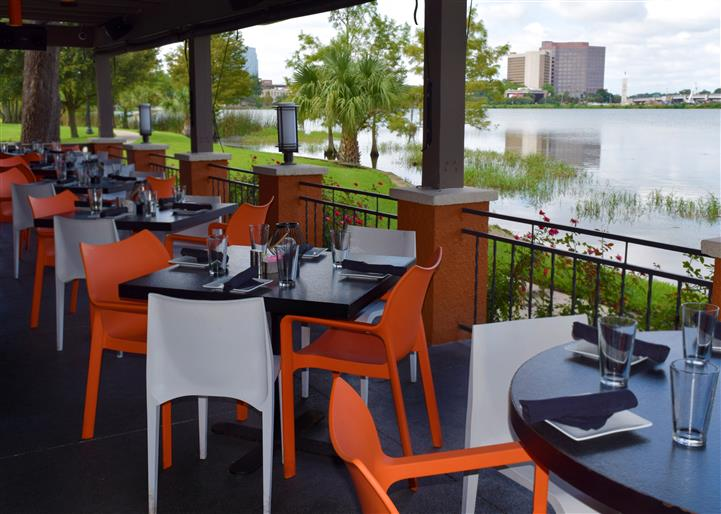 Outside shot of the restaurant's balcony with tables by the lake in the day
