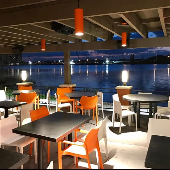 Outside shot of the restaurant's balcony with tables by the lake at night