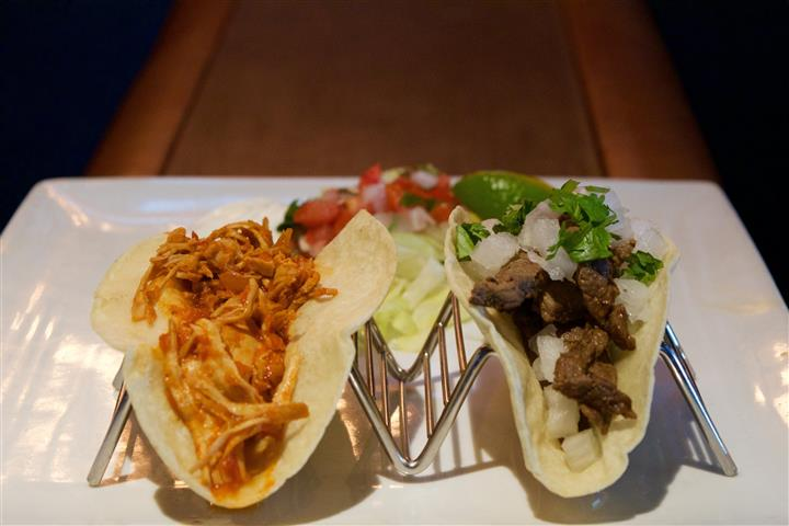 A shredded chicken and  a beef taco served with pico de galo and jalapeno