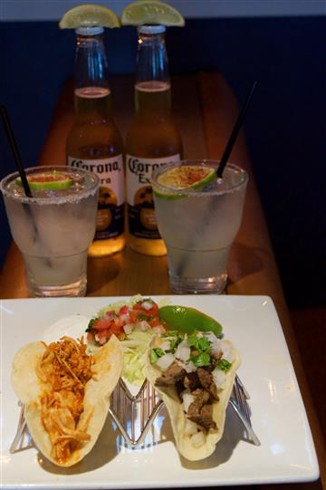 A shredded chicken and  a beef taco served with pico de galo and jalapeno, two glasses of white cocktail and to bottles of corona extra