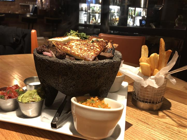 A meat dish served on a stone bowl surrounded with several dipping sauces and French fries