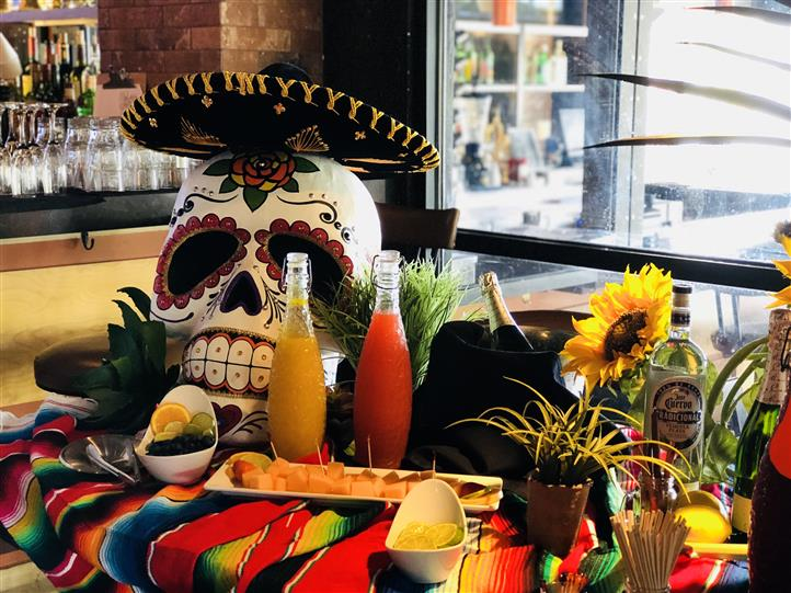 A yellow and a red bottle of drinks and a bowl with fruit beside a colored skull