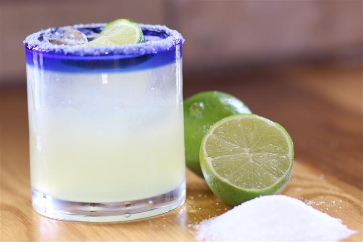 A glass of white cocktail beside two pieces of lime and salt