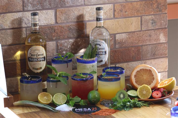 Glasses of cocktail surrounded of limes lemons and oranges, and two bottles of Jose Cuervo