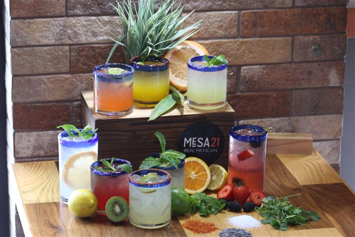 Glasses of cocktails surrounded by fruits