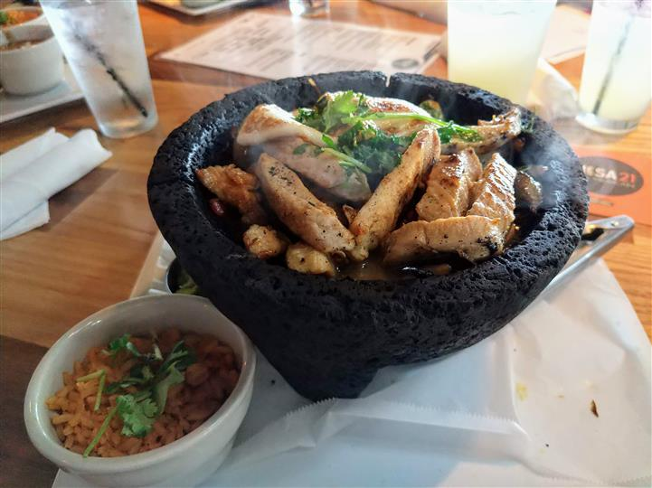 A meat dish served on a stone bowl next to a bowl of rice