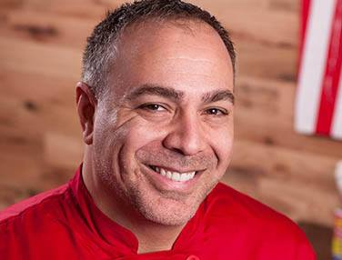Chef Ian Russo smiling for a photo wearing a red chef's jacket