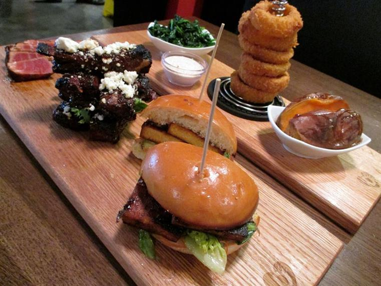 burgers, ribs and onion rings served on wooden boards