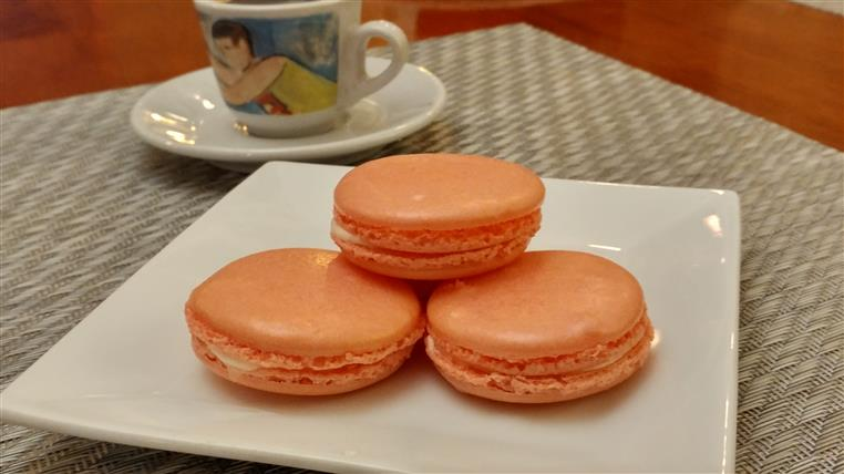 Three macaroons on square white plate in front of teacup on saucer.