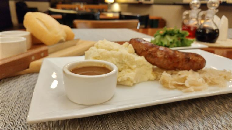 Housemade sausage with mashed potato and cup of gravy on white dish. Background is loaves of bread on cutting board, salad and vinegars.