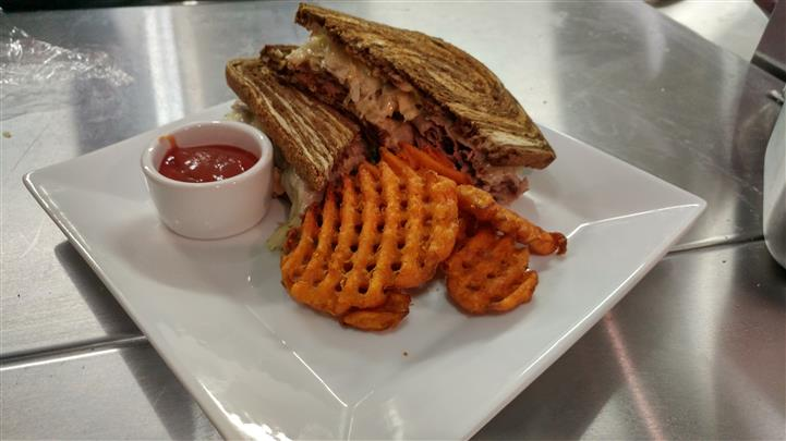 Classic reuben sandwich halved and served with sweet fries and ketchup