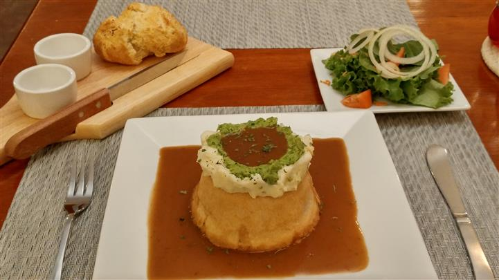 Pot pie topped with sauce or gravy, garlic mashed potato, smashed green peas