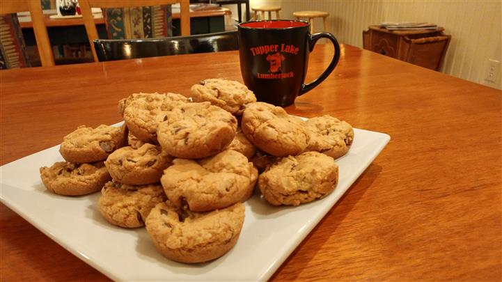 Chocolate chip cookies piled in a white plate next to a cup of coffee