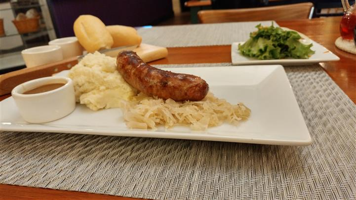 Bratwurst sausage served with sauerkraut and garlic mashed potatoes and gravy on the side