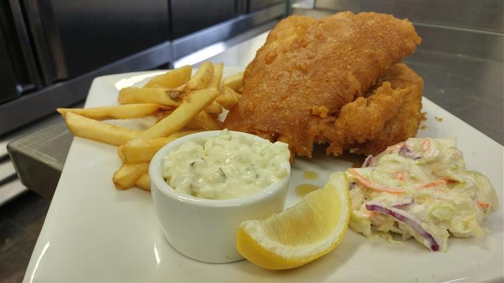 Fish and chips with tartar sauce, lemon, coleslaw on white dish