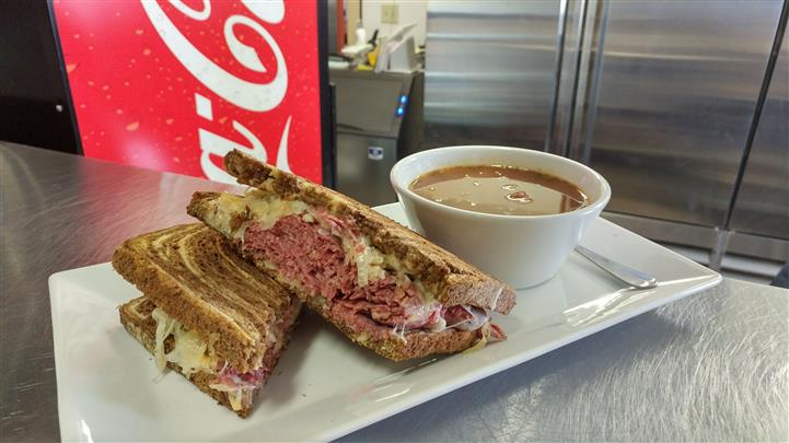 Reuben sandwich served with side of gravy on a white long plate