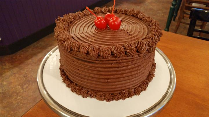 Chocolate cake decorated with chocolate frosting and cherries on top