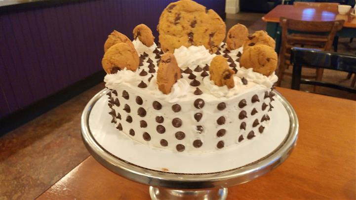 White frosting cake topped with chocolate chip cookies and drops of chocolate