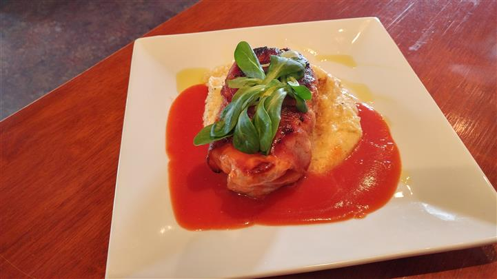Chicken dish served with mashed potatoes and tomato sauce with a garnish of greens