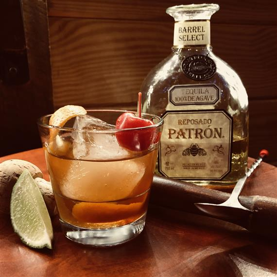 A bottle of Patron Tequila next to a glass of patron tequila topped with a cherry