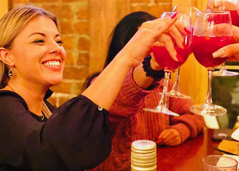 A woman smiling and raising her glass with her friends