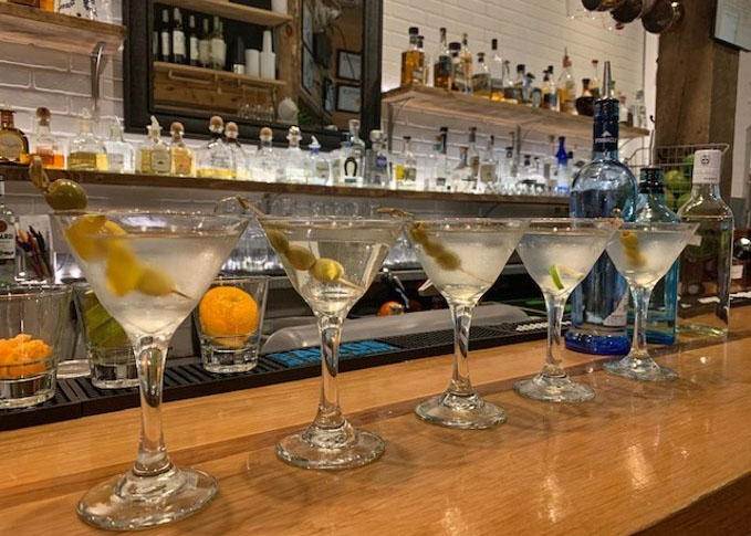 5 martinis with olives on top of the bar