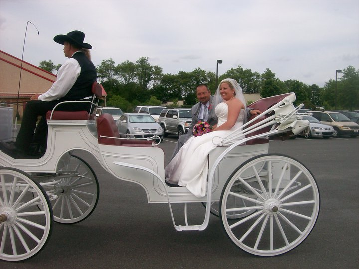 A bride and a groom on a white horse-drawn cab