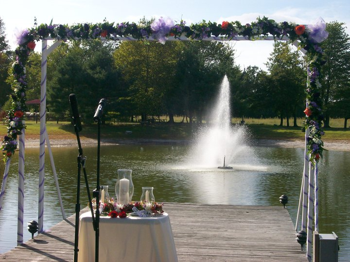 Wedding decoration and white chairs in frond of the lake with the fountain