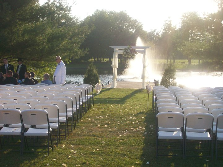 White wedding decoration and white chairs in frond of the lake with the fountain
