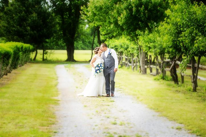 A wedding photo of a kissing couple at the field