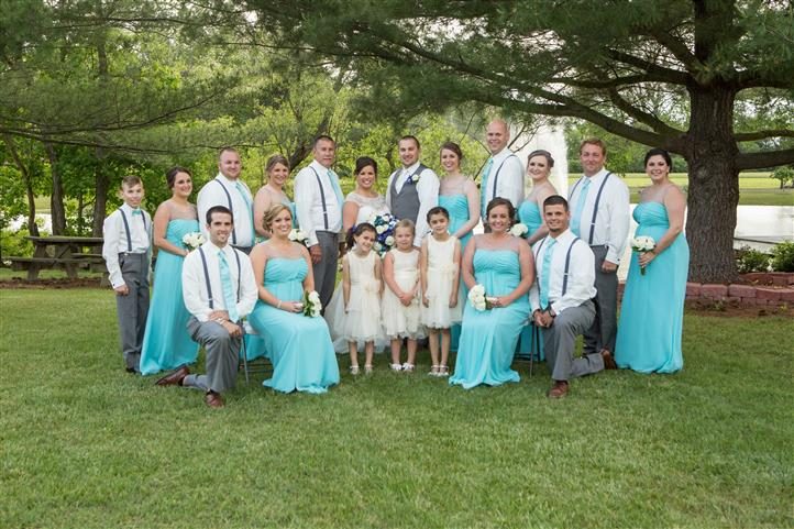 A wedding photo of men and women in light blue in the field