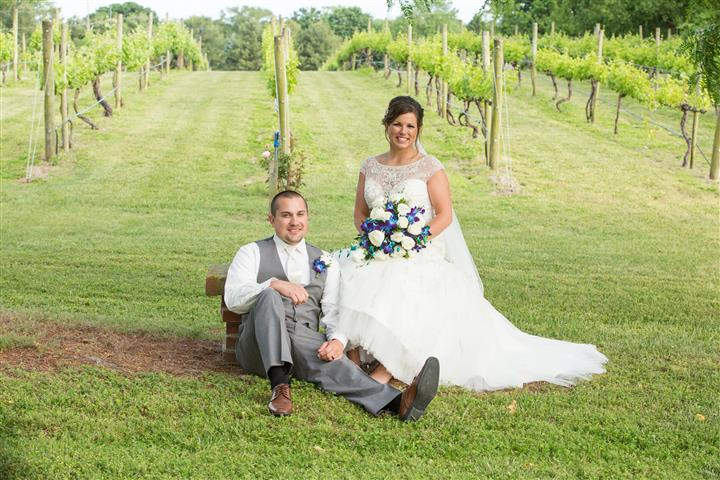 A wedding photo of a couple sitting at the vineyard