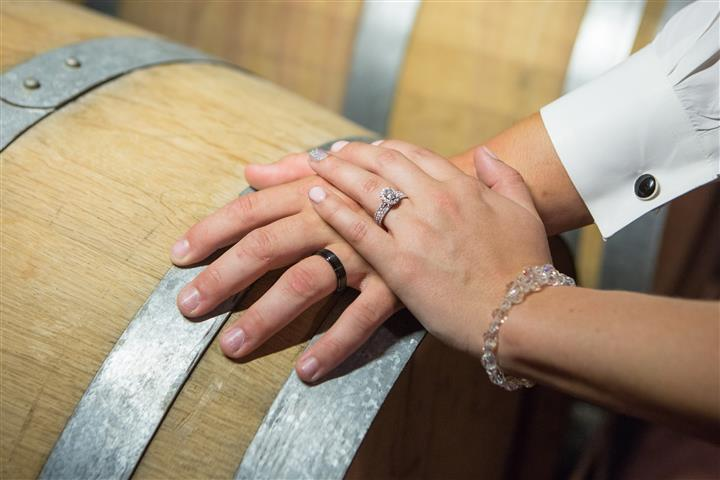 The hands of a bride and a groom on a wine barrel