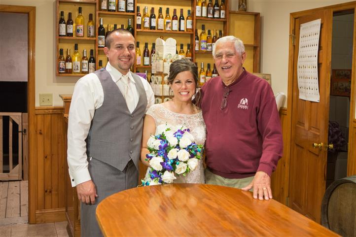 The bride and the groom with the winery owner posing for a photo
