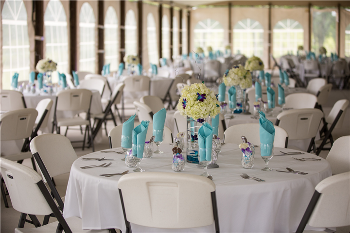 round tables with wedding decoration of white table cloths and flowers and light blue towels