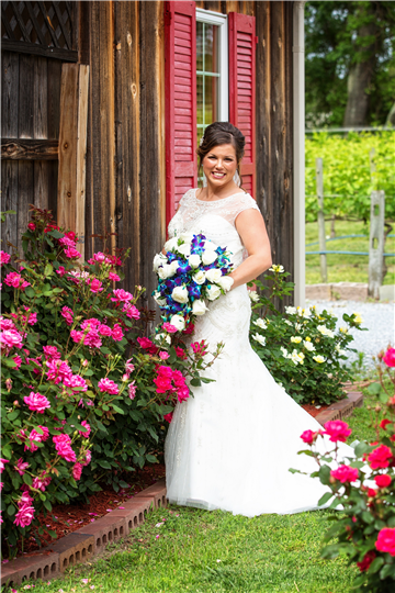 The photo of the bride by the pinks flowers in front of the building