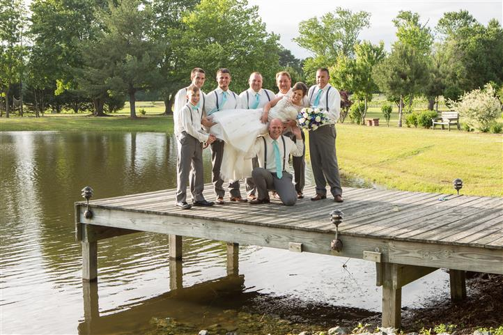 A wedding photo on the wooden bridge by the lake