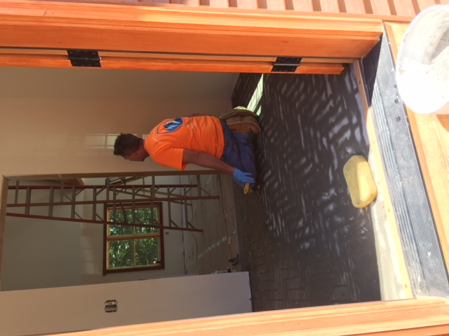 man on his knees installing tile