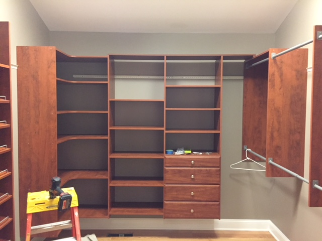 large walk-in closet with shelves and drawers
