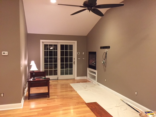 finished room with large door, ceiling fan