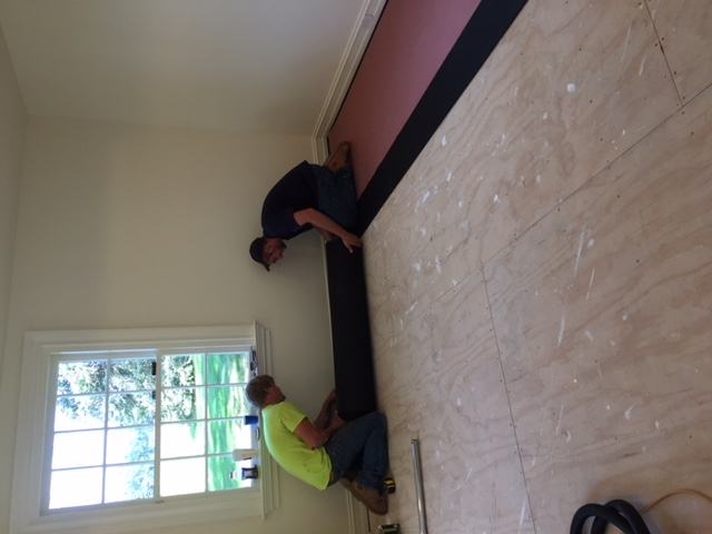 two men installing carpet